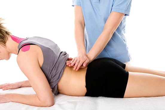 Image of a female patient and the hands of a professional kinetotherapist durng a massage session